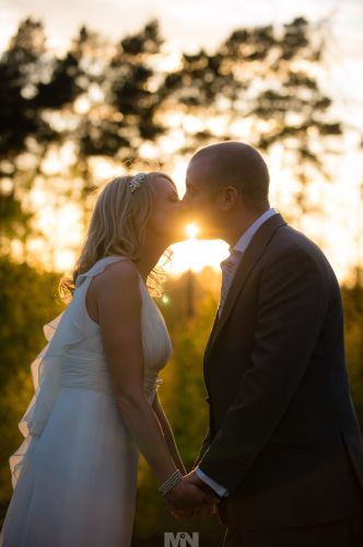 D2334-305-The bride_and_groom_share_a_kiss_at_sunset.
