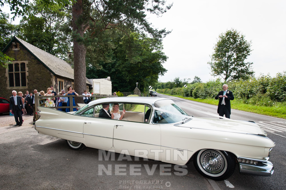 The happy couple leave the church in a vintage car.
