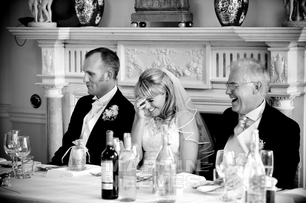 The bride laughs during the best man's spech.