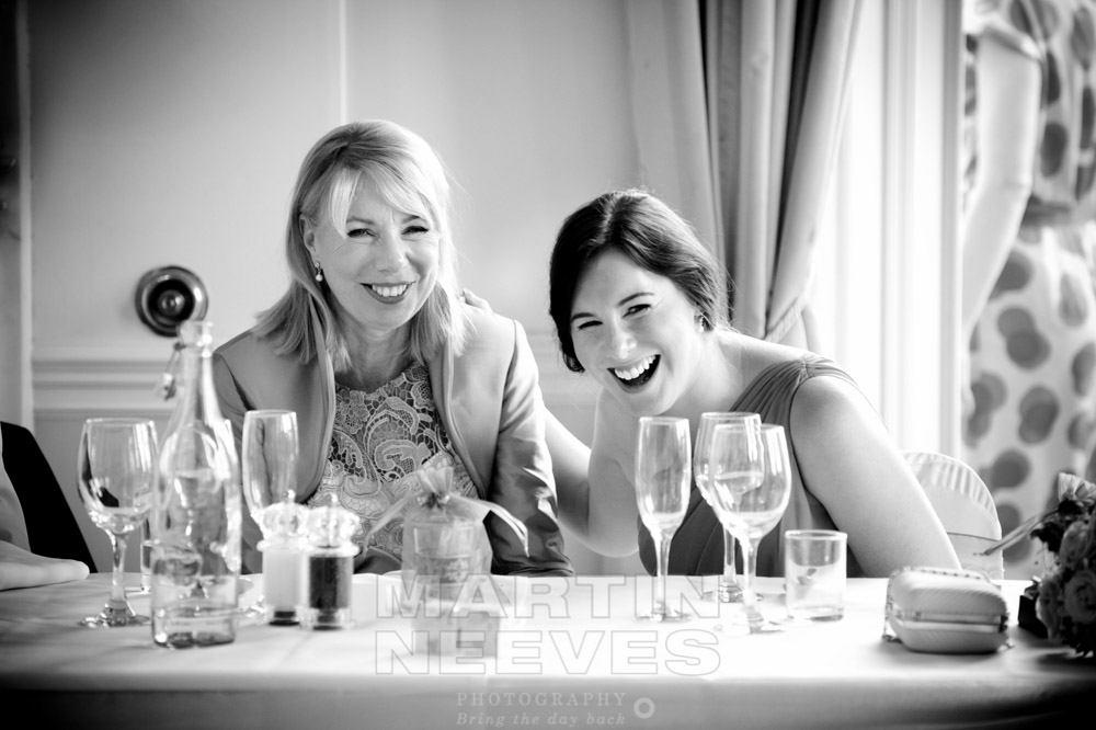 The bride's mother and twin sister laughing during the wedding reception at prestwold Hall.
