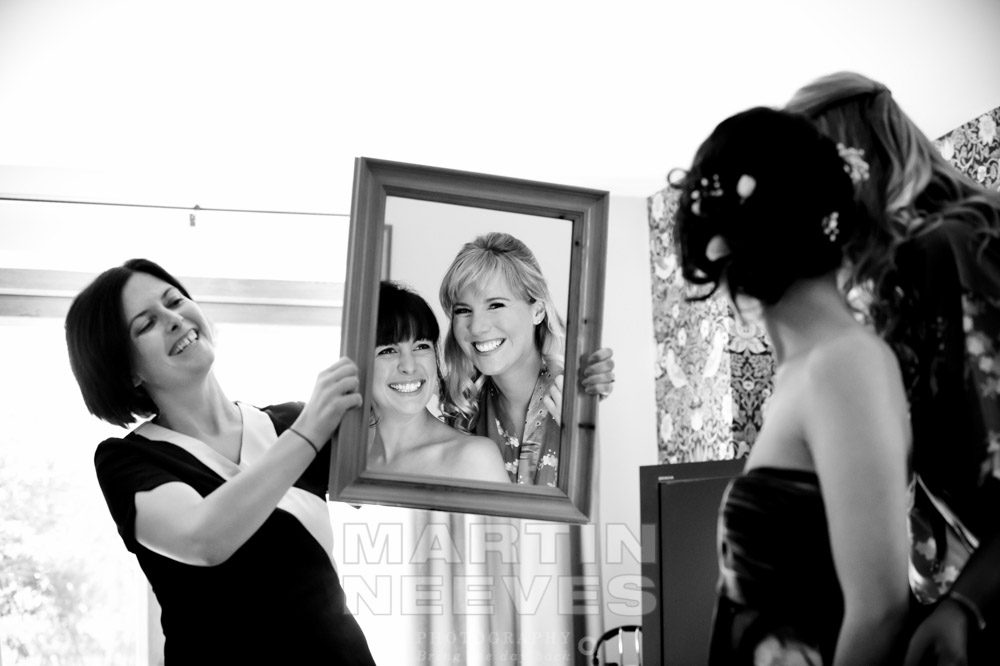 The make-up artist holds up a mirror for the bride and one of her bridesmaids.