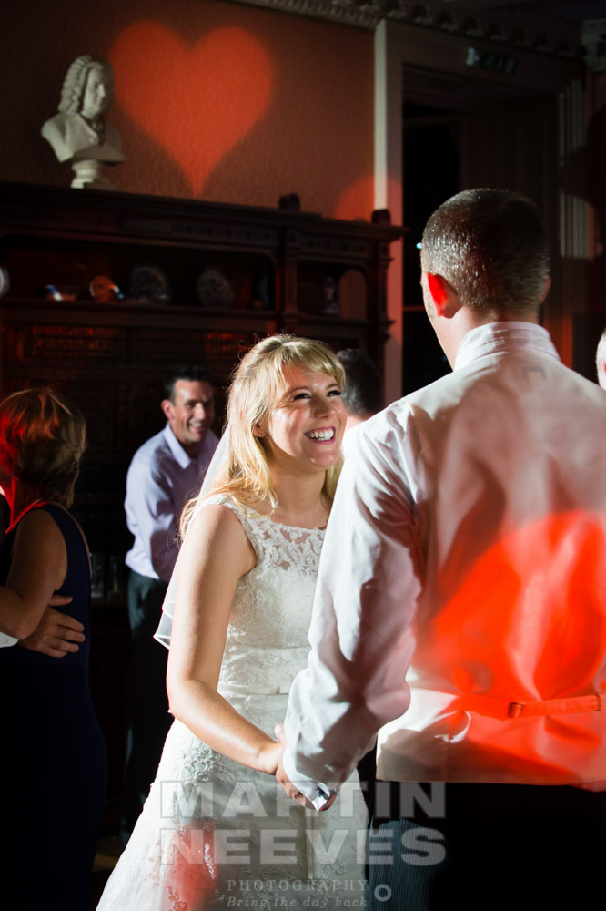 The happy couple have a dance while a red heart is projected onto the wall during the wedding disco.