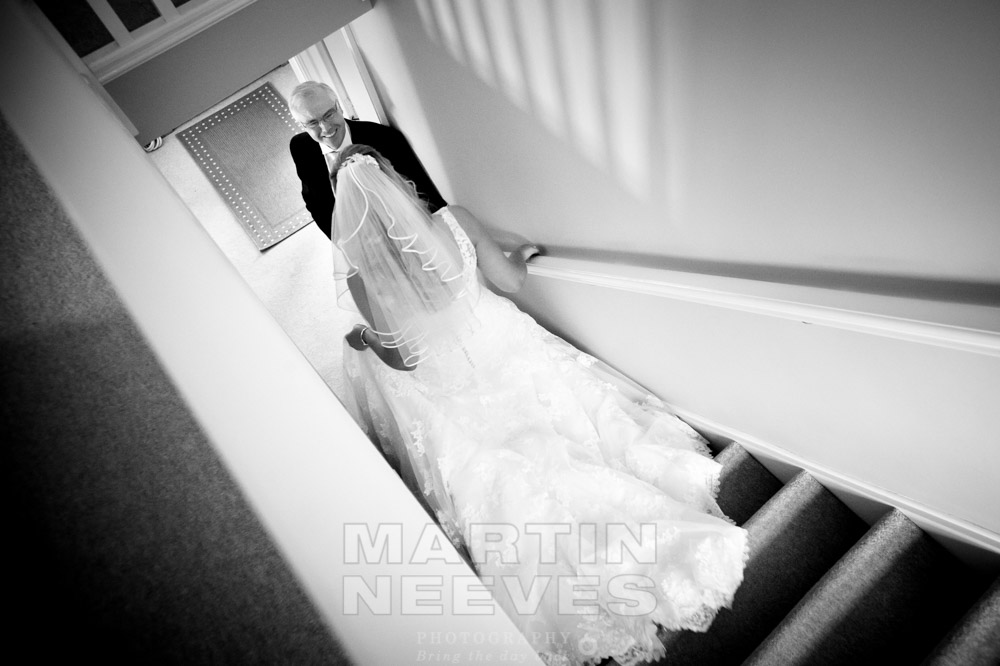 The bride's father sees his daughter in her wedding dress for the first time as she walks don the stairs.