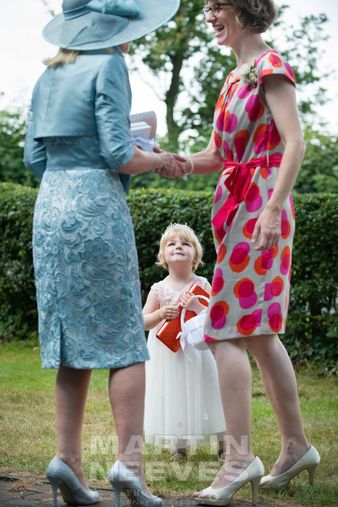 A young wedding guest looks after her mum's handbag.