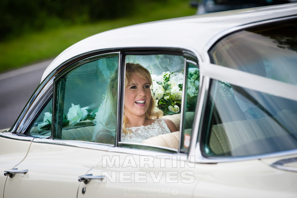 The bride arrives in a 1950's cream Cadillac.