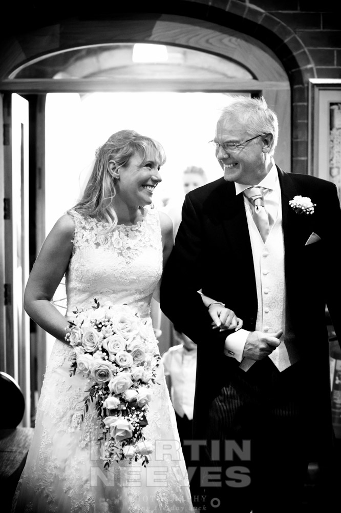 The bride and her father exchange smiles as they enter the church.