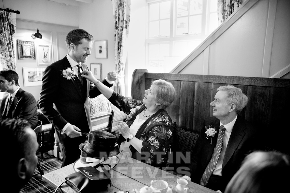The groom's mum makes some last minute sartorial adjustment's to her son's tie before the wedding ceremony.