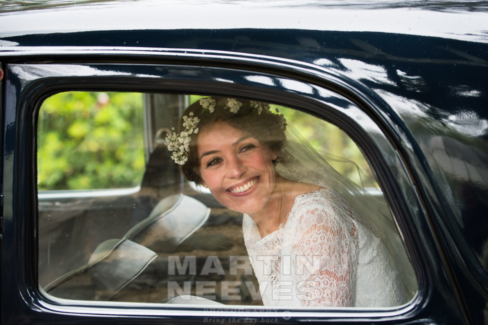 An excited looking bride arrives at the church in a vintage car.