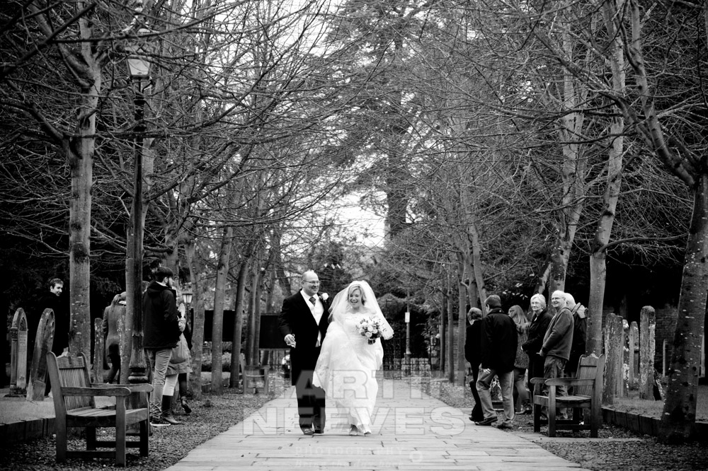 The bride and groom walk along the church path in Stratford-up0n-Avon, Warwickshire.