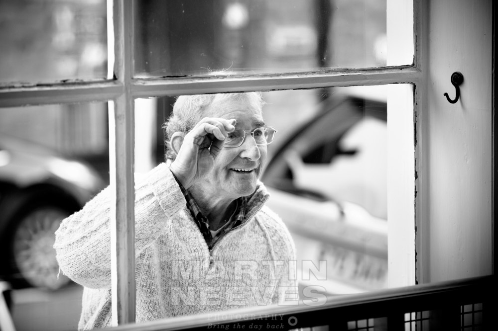 The bride's dad looks through the hairdressers window.