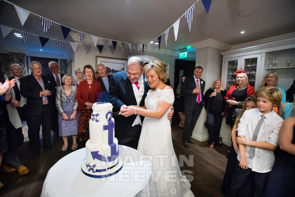The bride and groom cut their nautical-themed wedding cake.