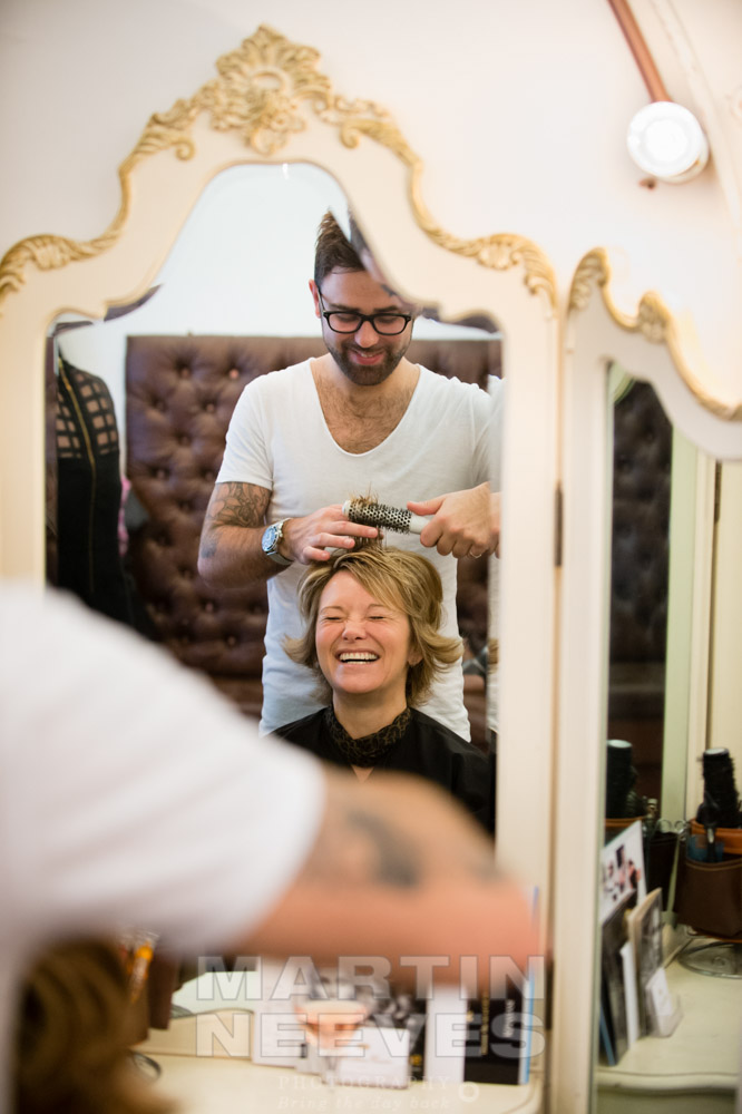 The bride laughs as she has her hair done.