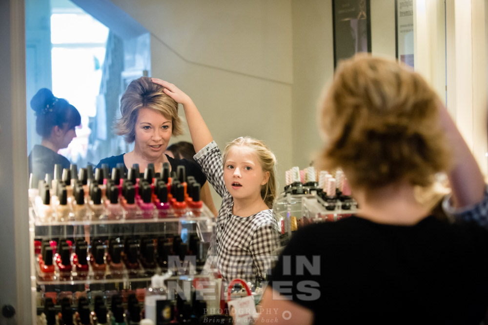 The bride's daughter helps her mum get ready.