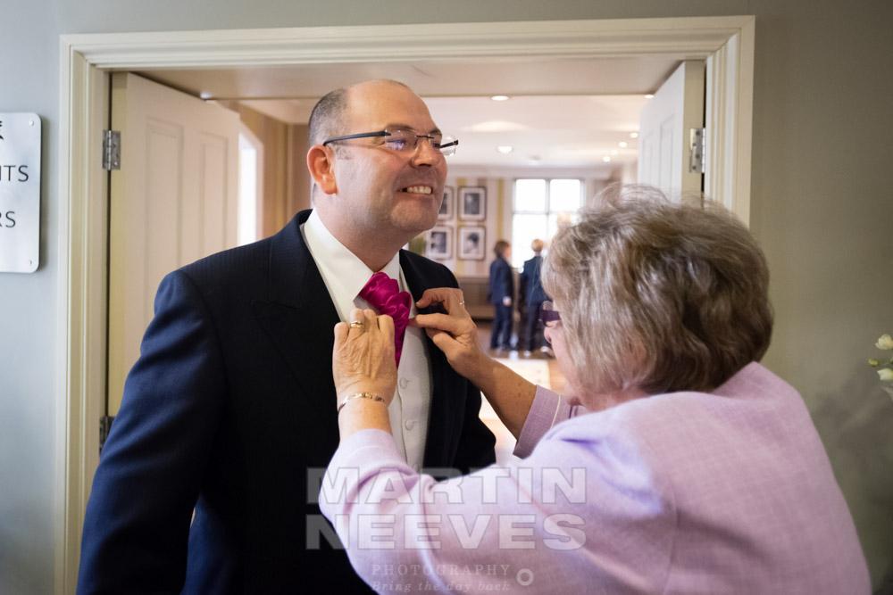 The grooms mum straightens her son's tie.